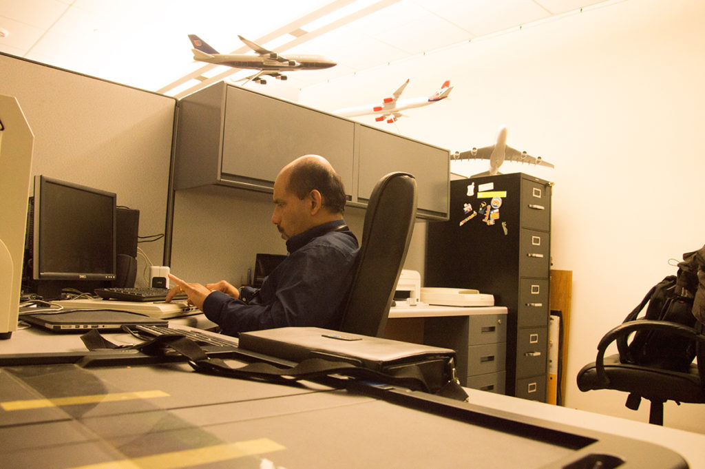 Bapin Working at his desk@HKNC. The aeroplane models kept in the background are from his collection.